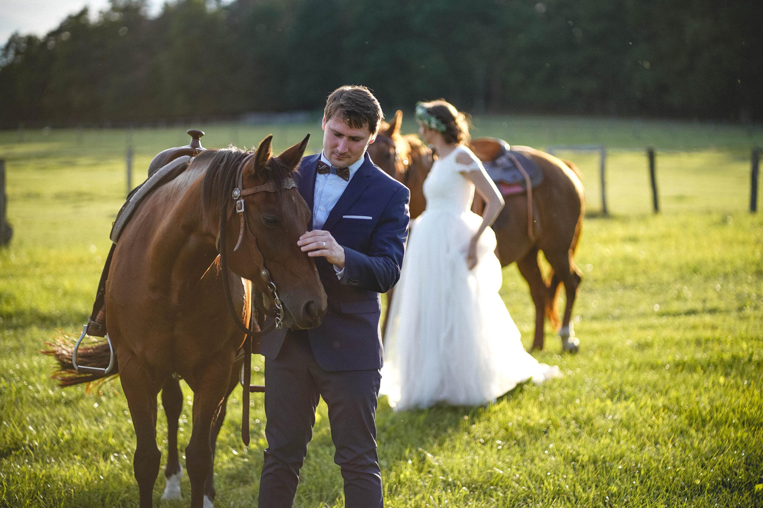 Nevěsta s ženichem se chystají na prijížďku na koních.